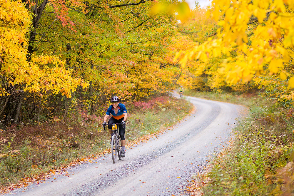 Biker on a winding gravel road, fall, unPAved bike race in central PA, fall bike competition, bike race in PA