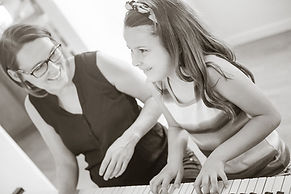 women and child playing piano