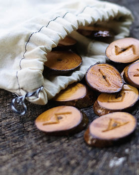 wooden runes in a bag on an old stump.jp