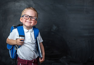 Happy cute clever boy in glasses with sc