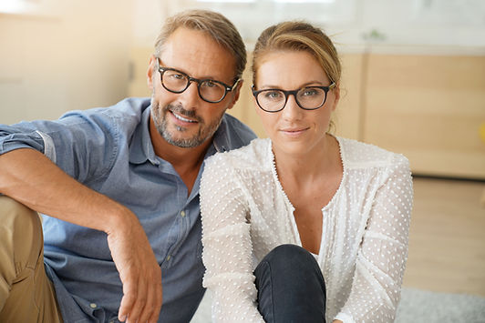Mature couple with eyeglasses sitting on
