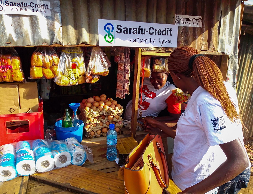 A regional officer showing a trader how to use M-Sarafu.