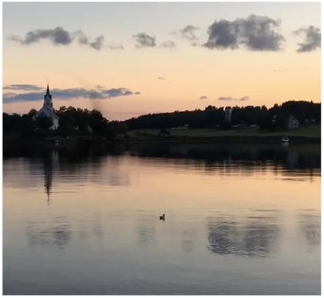 На фото видно воду, церковь, береговую линию с деревьями