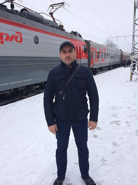 The man stands in front of train. Snow and cold.