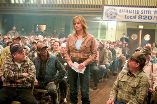 Кадр из фильма: женщина стоит в зале, вокруг сидят одни мужчины.