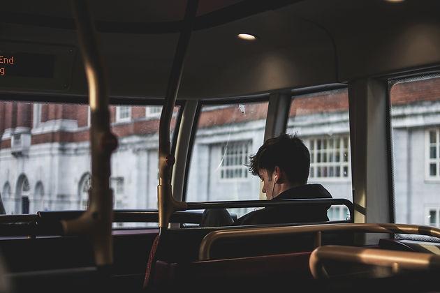 На фото виден парень в наушниках, он сидит в пустом автобусе.