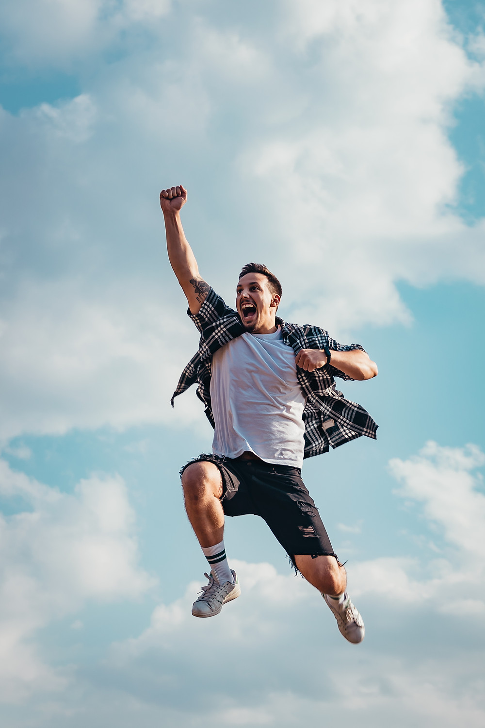 man jumping in the air for joy with a first pumped
