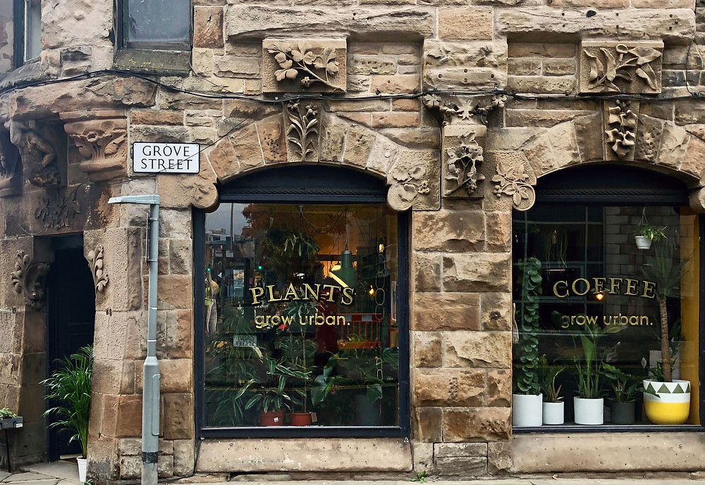 "Grow Urban is a fashionable industrial-style plant shop located in Edinburgh, UK. Plants fill the windows of this plant shop with the words ""plants"" and ""coffee"" printed on the glass."