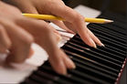 pencil and piano and hands songwriting.j