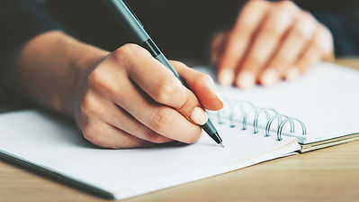 Person writing in a spiral notebook with a ballpoint pen