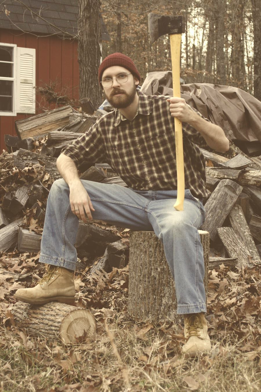 Chance sits on stump with axe in front of wood pile