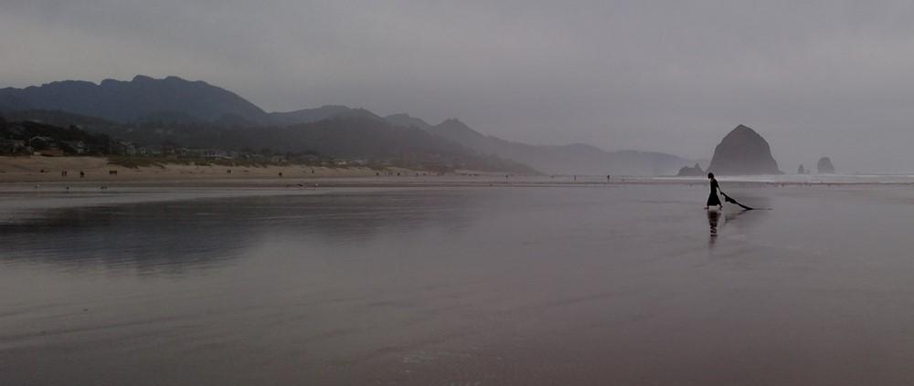 Woman Dragging Black Flag on Beach