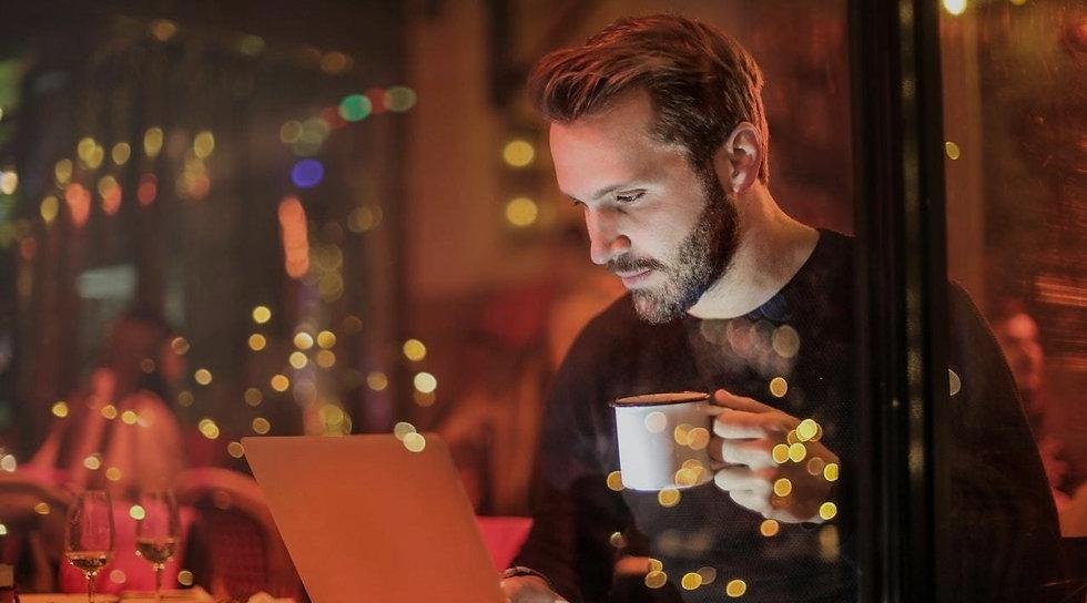 man-holding-mug-in-front-of-laptop-84254
