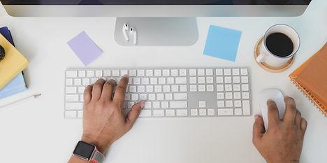 Blick von oben auf einen Tisch mit Hand auf Computertastatur und auf einer Apple Magic Mouse