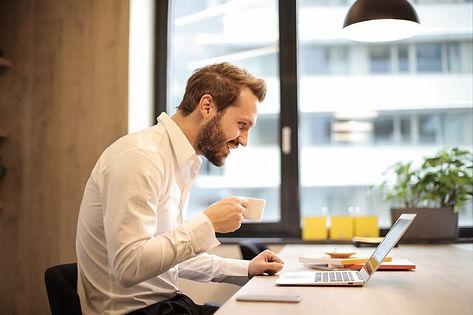 Mann sitzt mit Tasse Kaffee in der Hand vor einem Notebook