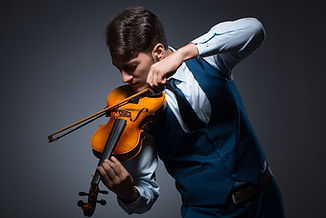 Young man playing violin in dark room.jp