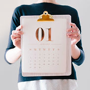A person holds a calendar showing a date on a clipboard