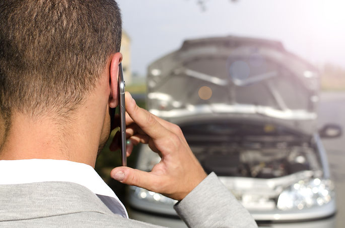 man-standing-by-broken-vehicle-calling-tow-service.jpg