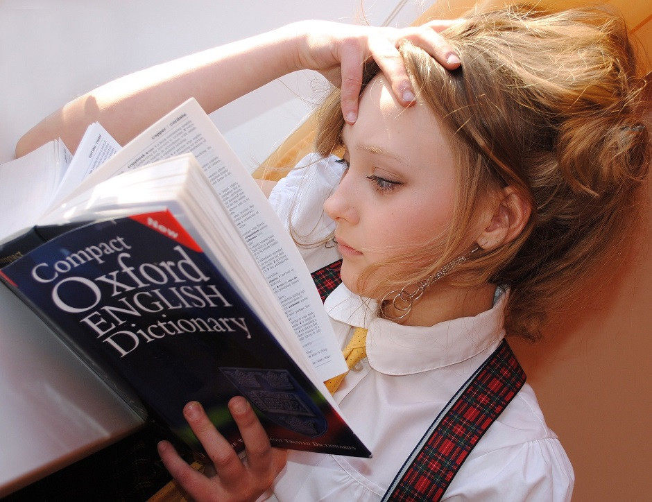 Girl reading dictionary to find better words to use in her marketing copy