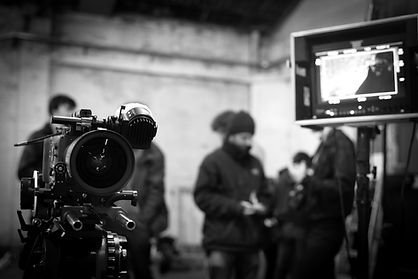Arri Alexa in foreground with crew and monitor out of focus behind