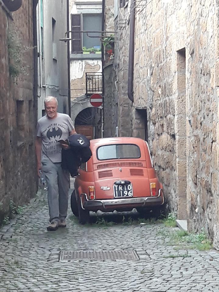 Svein bruker seg selv som målestokk for størrelsen på en Fiat 500 av klassisk årgang.