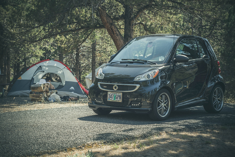 Mercedes Benz smart car with Oregon license plate sitting in paved parking area of a forest campground besides pitched tent