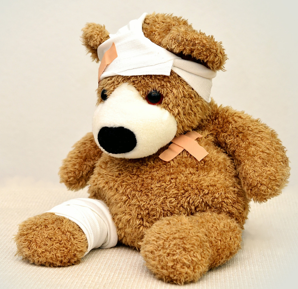 Teddy bear with fake wounds covered with bandaids and ace bandages