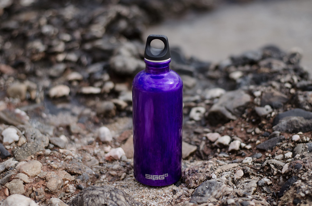 Purple Sigg brand insulated water bottle with twist off top sits on surface covered with fractured rocks