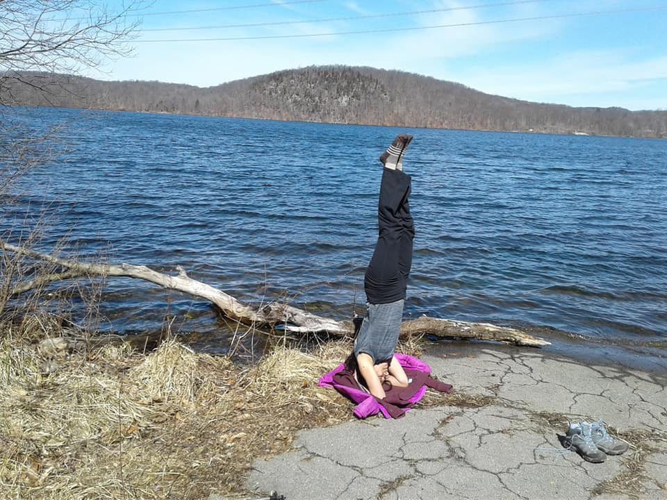 Young woman does Headstand yoga pose along a trail next to a lake in near Catskills, NY.