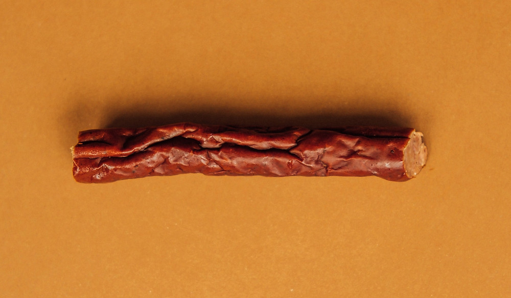 Split piece of pepperoni beef jerky stick on top of an orange piece of parchment paper
