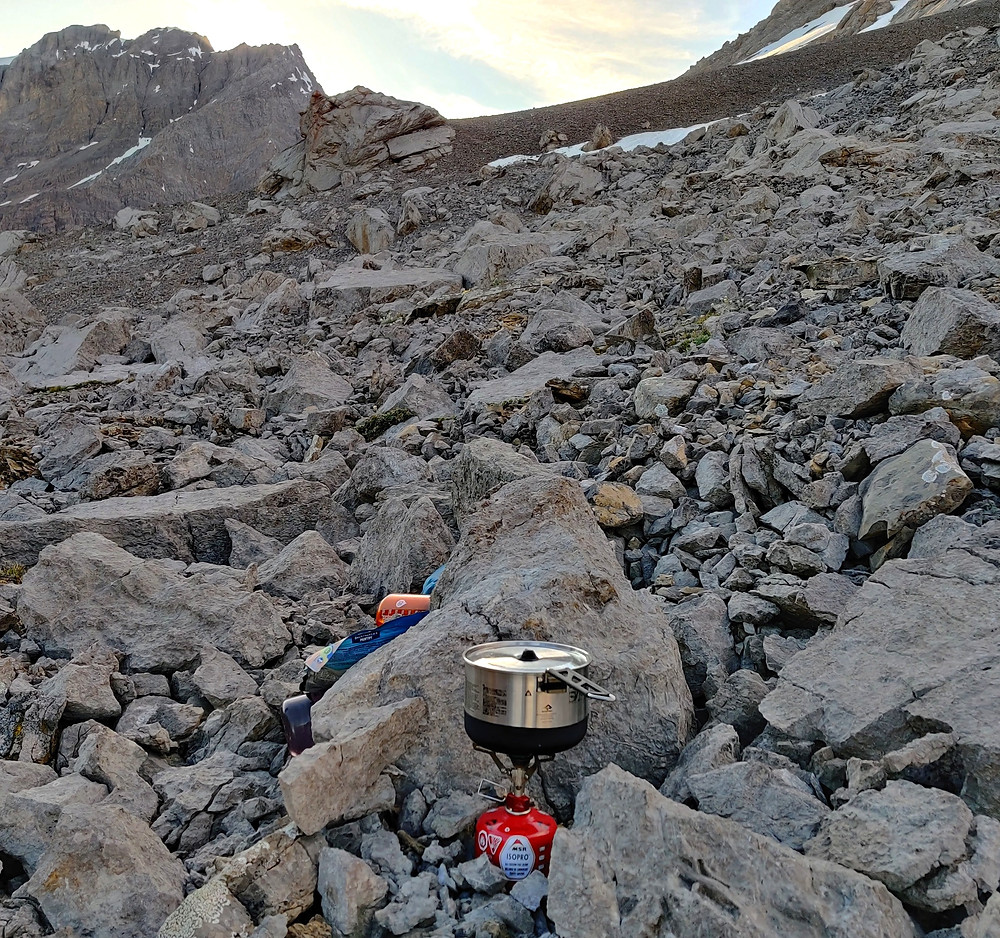 Jetboil camping stove set up in boulder field at dusk with nearby camping gear