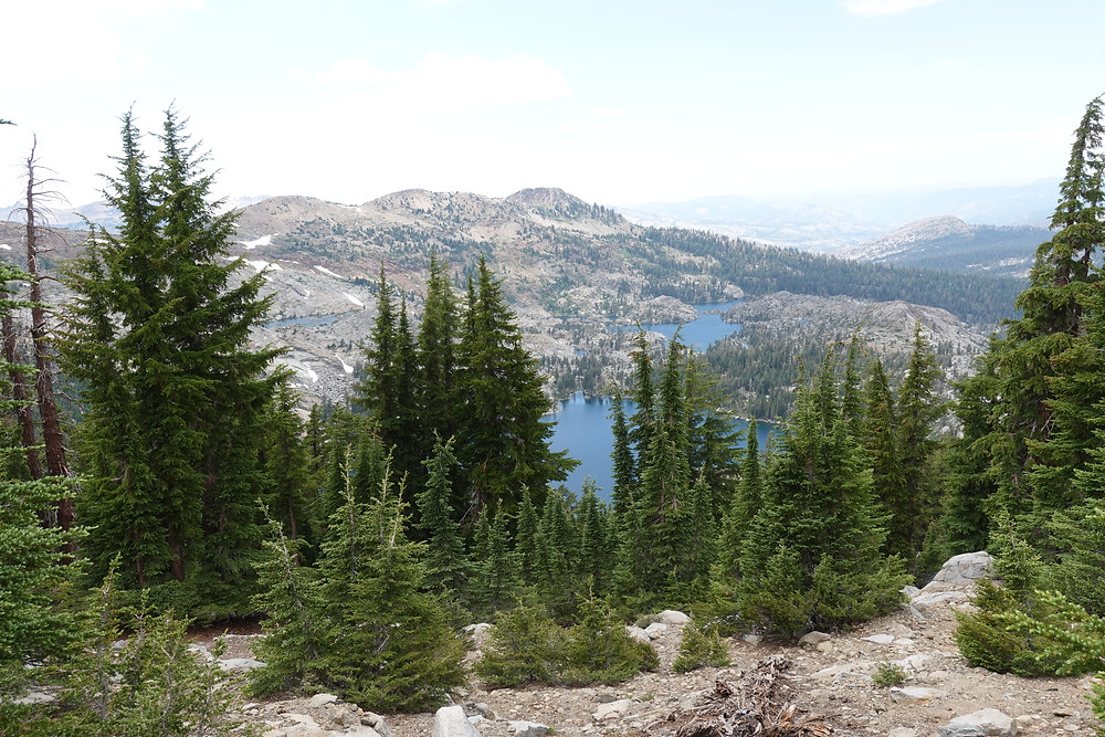 A clearing of trees along a hiking trail opening the view to multiple deep blue lakes among rolling mountains below