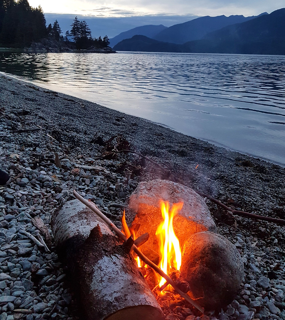 Well-lit rock and stick campfire steps from the water of a large alpine lake surrounded by mountains in Montana
