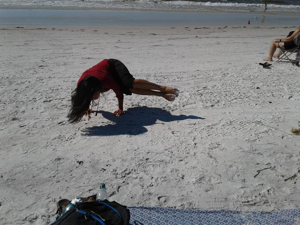 Young woman doing a Side Crow Yoga Pose on the beach at Clearwater, Florida