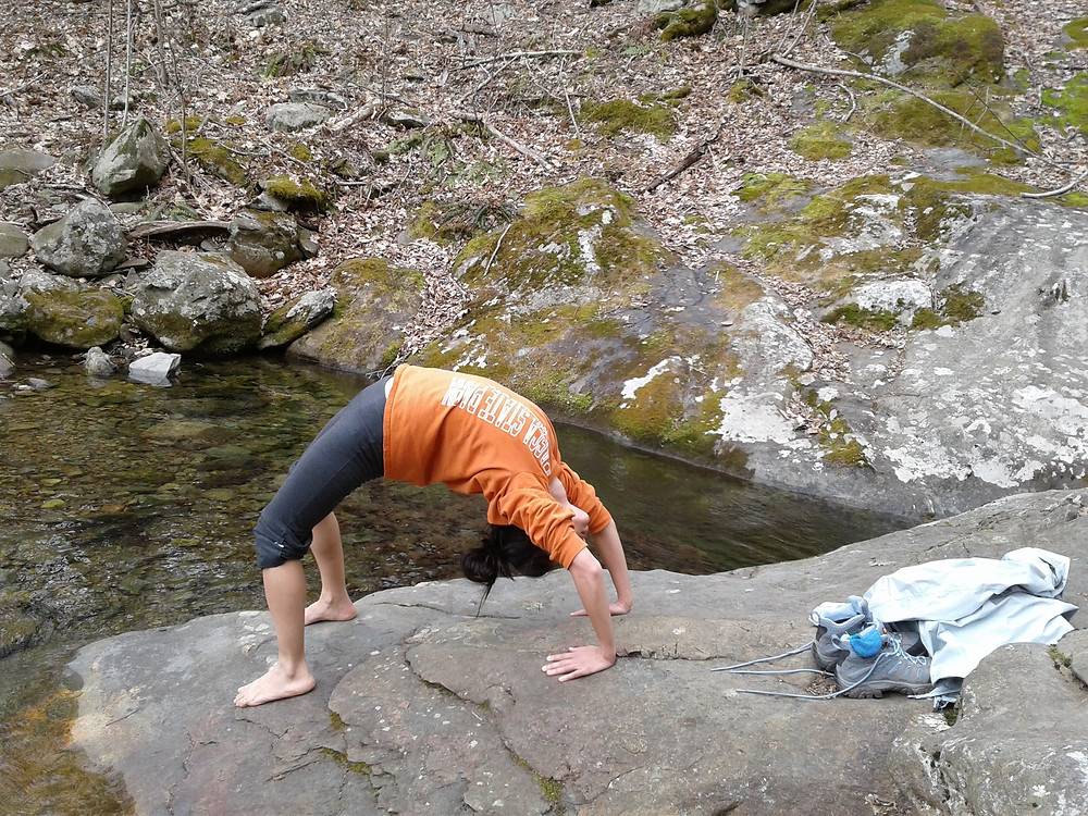Young female hiker doing a wheel yoga pose beside a river in Shenandoah National Park