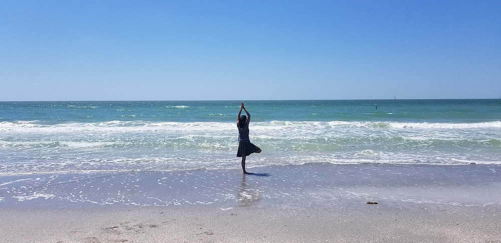 Young woman doing tree pose yoga position on a coastal hike in Clearwater, Florida