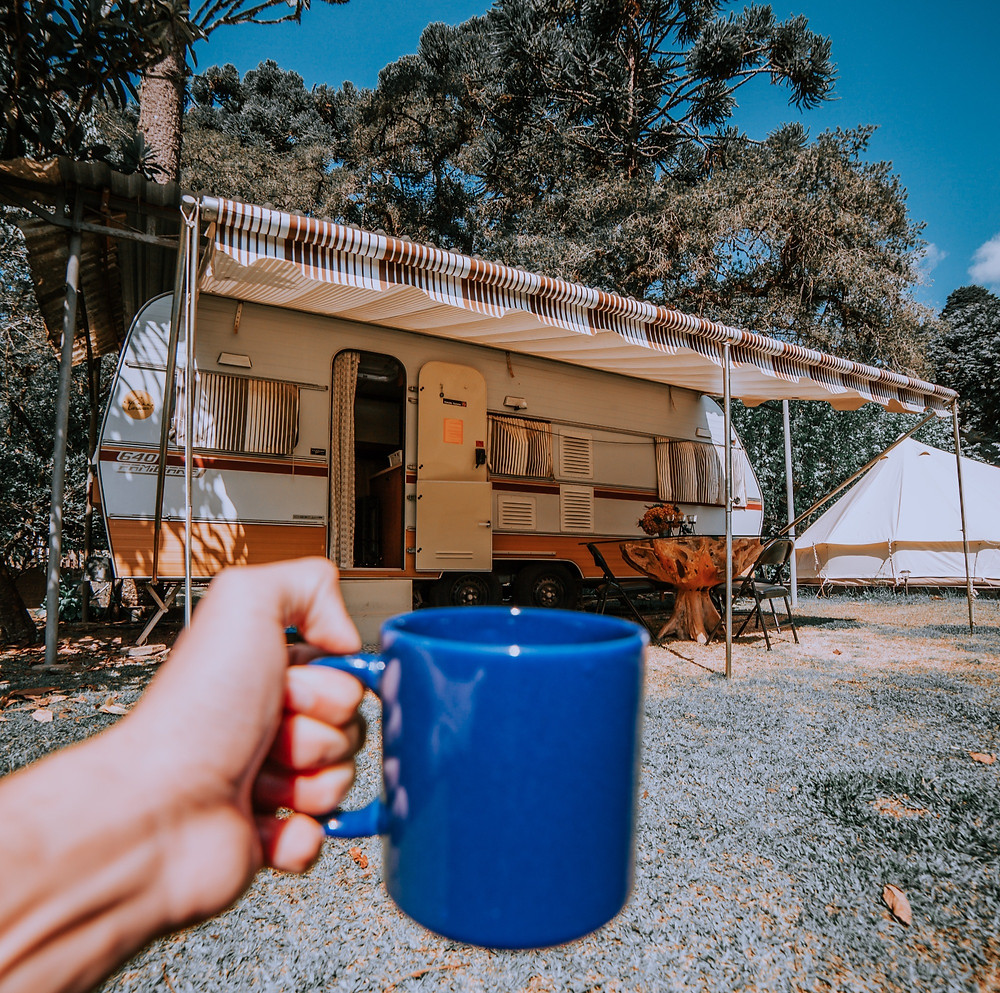 Young person holding up blue mug next to G40 RV camper with awning setup in the forest