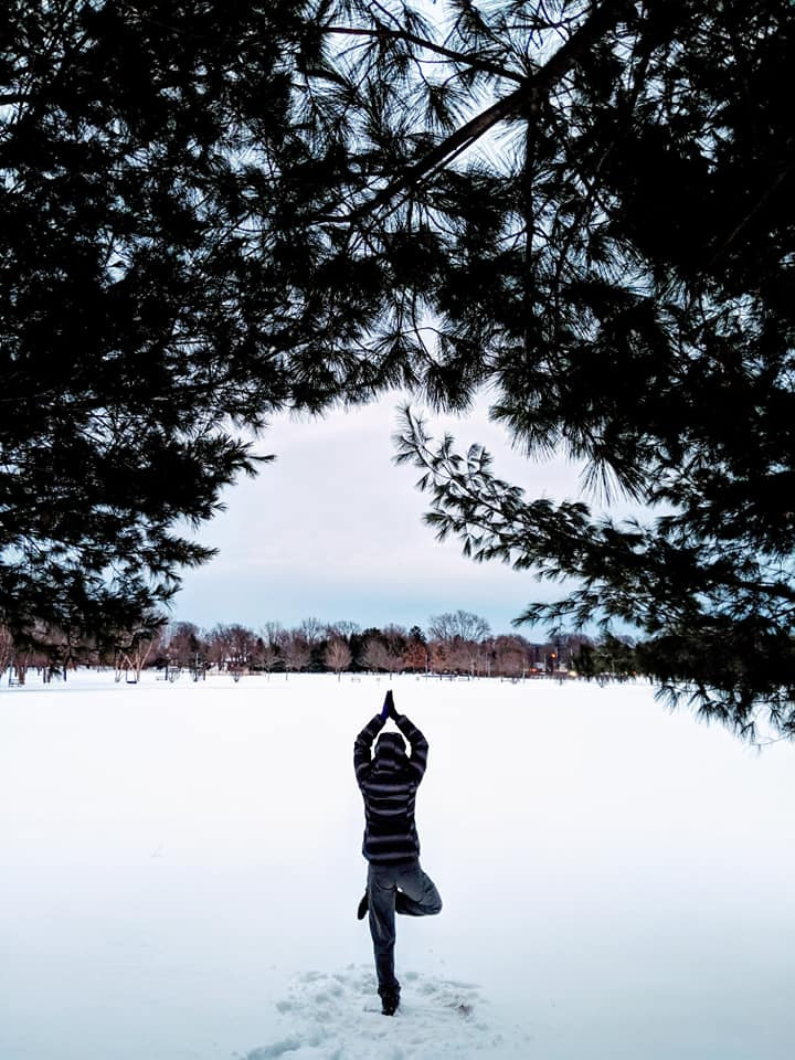 Young man doing Tree Yoga Pose in the snow at Colonie Park in Albany, New York