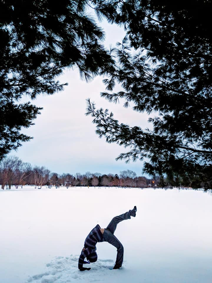 Young man doing Wheel Yoga Pose in the snow at Colonie Park in Albany, New York