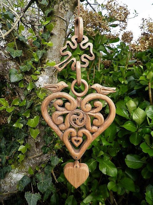 Coeur de naissance au triskell entouré de esses surmonté d'un trèfle.