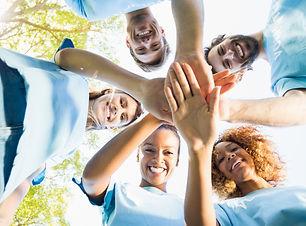 Portrait of volunteer group forming hudd