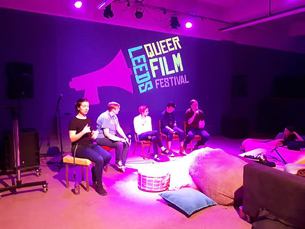 Four people participate in a Q&A at Leeds Queer Film Festival, while someone provides BSL
