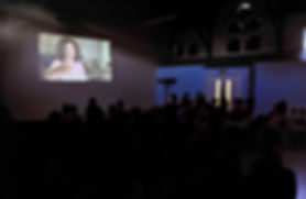 People sitting in a darkened room watching a film with subtitles