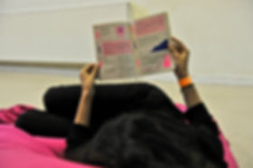 An image of someone lounging on a bean bag reading the Leeds Queer Film Festival Programme