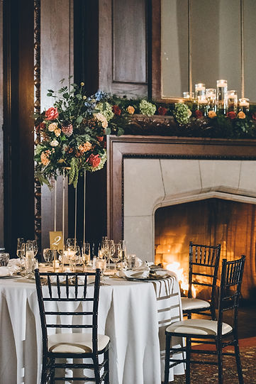 Wedding table setting by a firelit fireplace.