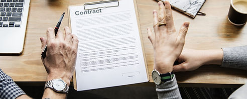 Two people filling out a contract.