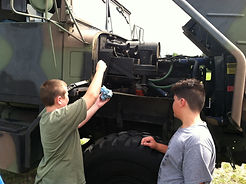 Kids fixing military truck