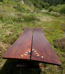 This table comes from the same log: base and table top. It is 11 feet long by 46 inches wide at max. I have inlayed snow geese flying in formation as they do and a few on the base taking flight.