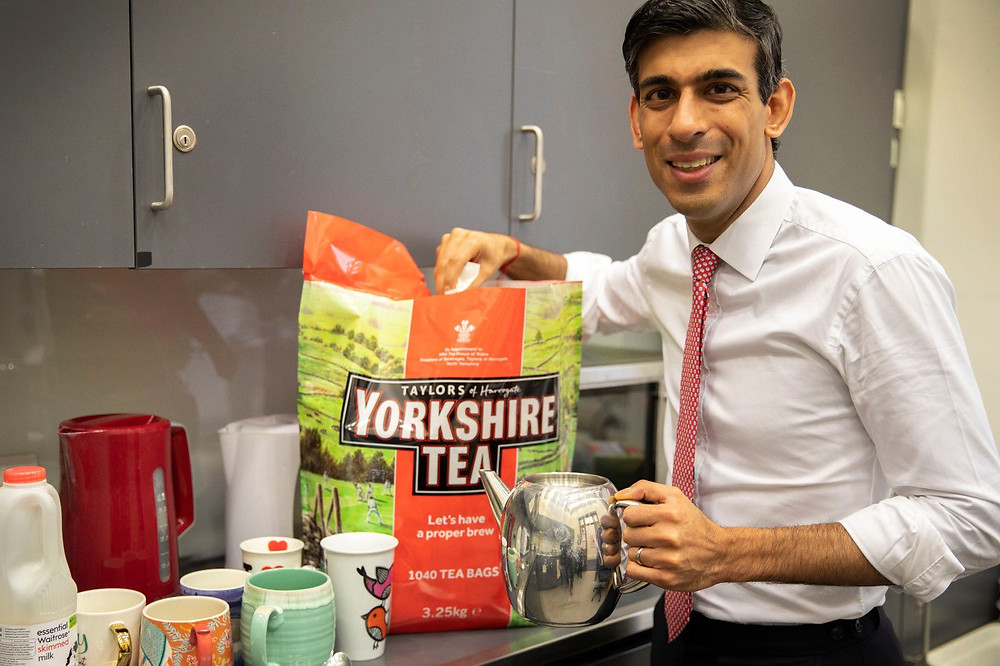 Chancellor of the Exchequer Rishi Sunak holding a kettle in one hand and a large bag of Yorkshire Tea in the other.
