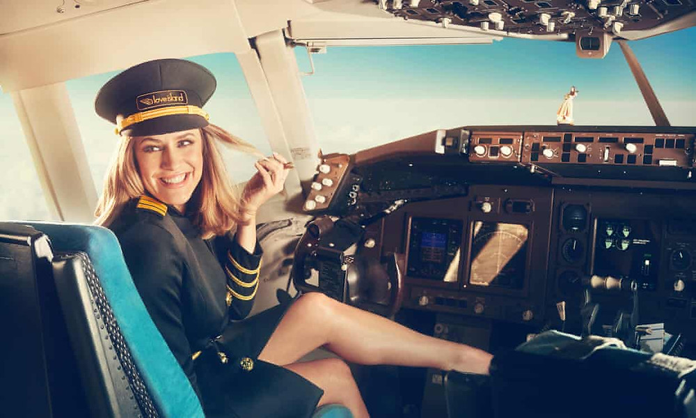 Late presenter Caroline Flack in a promotional image for Love Island. She's sat in the cockpit on a plane wearing a pilot's uniform. She's smiling at someone out of shot.